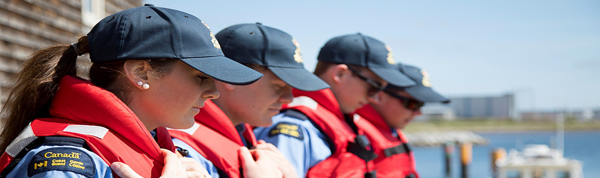 Officer cadets in life jackets, standing by the waterfront.