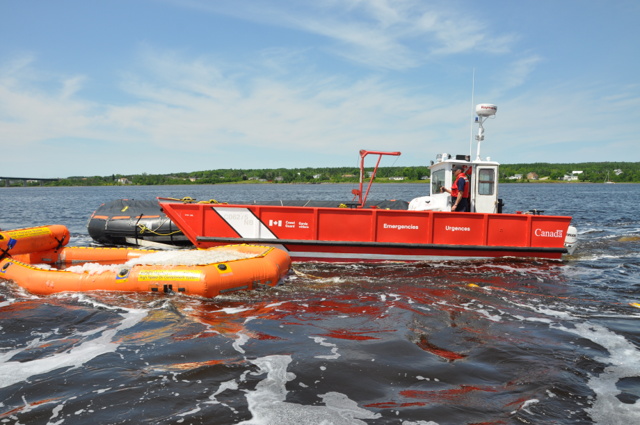 Environmental response vessel setting up oil containment equipment