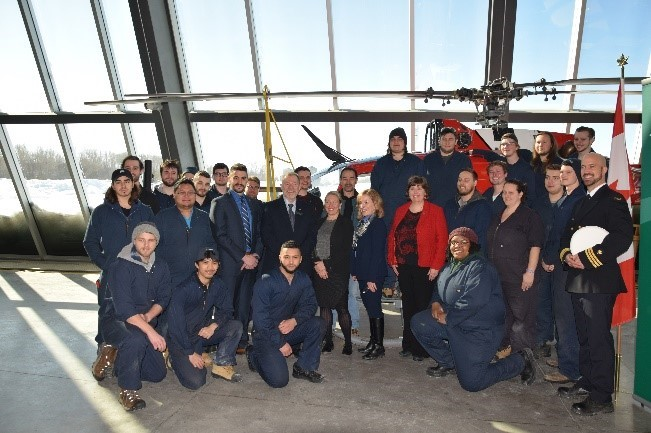 Algonquin College students pose with a donated BO 105 helicopter with instructor Serge Côté, MPs Anita Vandenbeld and Mona Fortier, and other esteemed guests.
