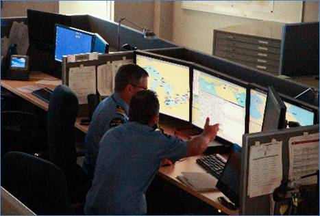 Marine security operations centre employees working at their stations.